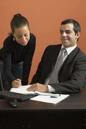 Office woman showing a businessman paperwork as he looks at her. Vertically framed photo. Stock Photo