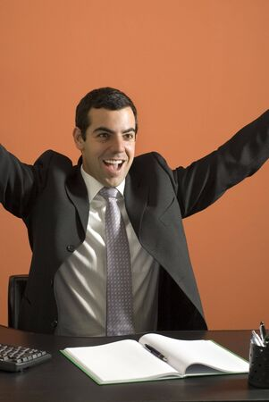 jubilation: Smiling businessman seated at his computer throwing his arms up in jubilation. Vertically framed photo. Stock Photo