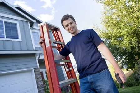 sufficient: Smiling man standing in front of house holding ladder and hammer. Horizontally framed photo.