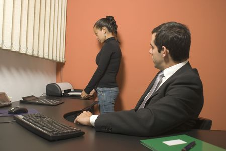vertically: Woman using a fax machine while a businessman watches from his desk. Vertically framed photo. Stock Photo