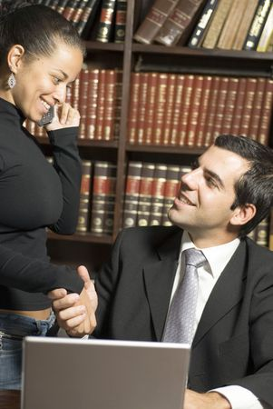 Man and woman shake hands over laptop. They are smiling at eachother while she is on the cellphone. Vertically framed photo. photo