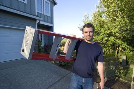 Smiling man standing in front of house holding ladder and hammer. Horizontally framed photo.