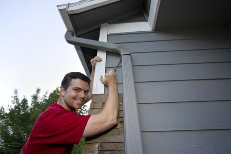 Smiling man leaning against a house working with a screwdriver. Horizontally framed photo.