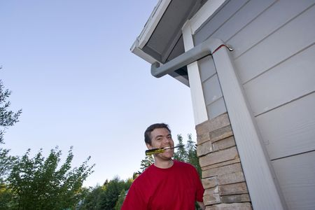 Man  with a screwdriver in his mouth and a smile on his face. Horizontally framed photo photo