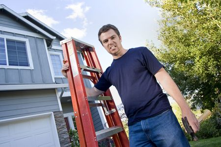 Unhappy man standing in front of house holding ladder and hammer. Horizontally framed photo. photo
