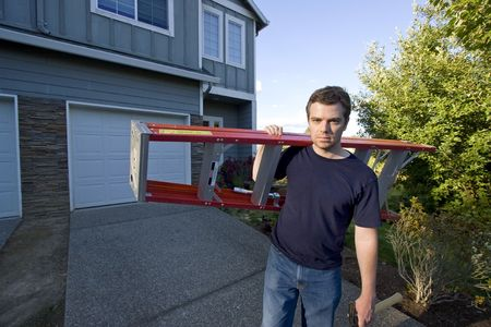 Frowning man standing in front of house holding ladder and hammer. Horizontally framed photo.