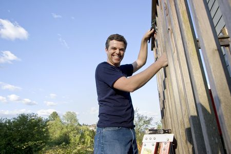 sufficient: Smiling man on a ladder repairing siding of a house with a wrench. Horizontally framed photo.