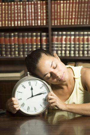 vertically: Female student sleeping in an office on a clock. Vertically framed photo. Stock Photo