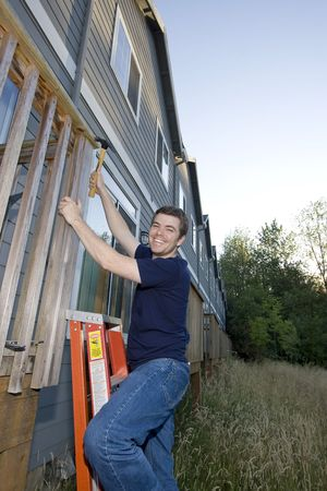 sufficient: Smiling man on ladder hammering a porch. Vertically framed photo.