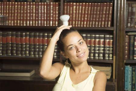 Smiling girl with lightbulb on her head. Horizontally framed photo. photo