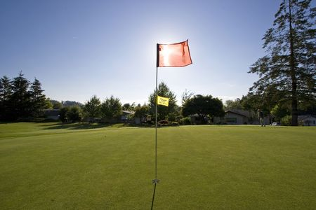 blocking: View of a golf course as the sun is going down.  The flag is blocking the sun.  Horizontally framed shot. Stock Photo