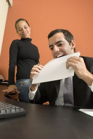vertically: Businessman jokes around by putting a paper in his mouth as his co-worker watches. Vertically framed photo