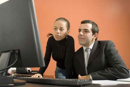 Businessman and woman looking at a computer. Horizontally framed photo.