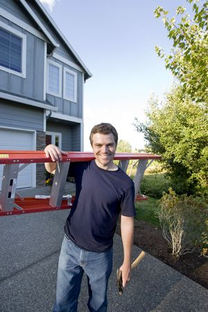 Smiling man standing in front of house holding ladder and hammer. Vertically framed photo.