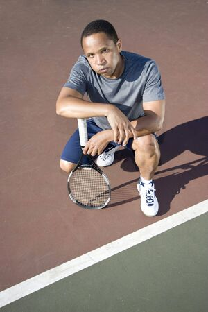 1 person: Tennis player crouching down looking defeated and sad, he holds his tennis racket in his hands. Vertically framed photo. Stock Photo