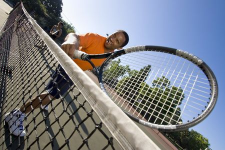 Man holding his racket and smiling, his partner is in the background in a ready stance. Horizontally framed photo. photo