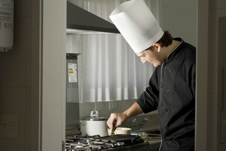 Chef standing over a stove holding parsley above a griddle. Horizontally framed photo. Stock Photo - 3878237