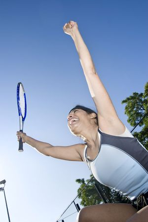 Female tennis player smiling and jumping with her hands up in the air in celebration. Vertically framed photo. photo