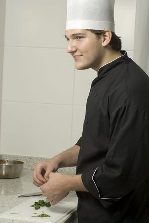 Young chef holding parsleyon a cutting board on a counter top. Vertically framed photo. Stock Photo - 3878243