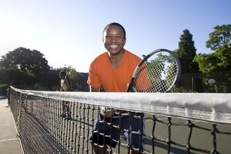 Man playing tennis. He holds his racket and stands near the net as he smiles. Horizontally framed photo. Stock Photo - 3883492