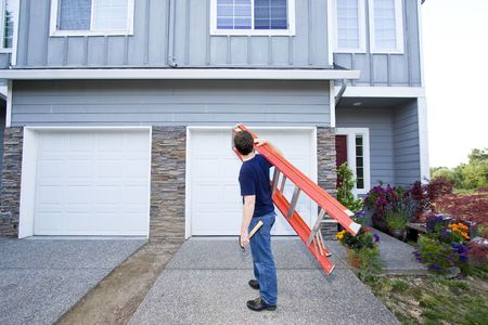 sufficient: Man standing in front of house holding ladder and hammer. Horizontally framed photo.