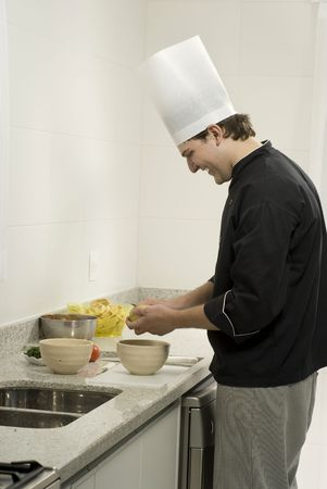 Young, smiling, chef  peeling potatoes into a bowl on a counter next to a bowl and tomatoes. Vertically framed photo. Stock Photo - 3883198