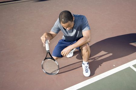 Tennis player crouching down looking defeated and sad, he holds his tennis racket and hangs his head down. Horizontally framed photo. Stock Photo