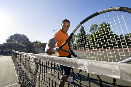 Man holding his racket and smiling, his partner is in the background in a ready stance. Horizontally framed photo. Stock Photo