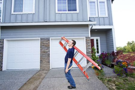 sufficient: Laughing man standing in front of house holding ladder and hammer. Horizontally framed photo. Stock Photo