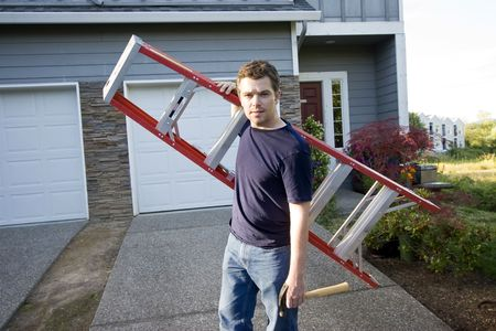 home improvement: Man with a serious look on his face standing in front of house holding ladder and hammer. Horizontlly framed photo.