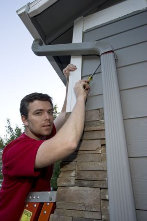 Man standing on a ladder fixing a house with a screwdriver. Vertically framed photo. photo