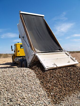 truck: A dump truck is dumping gravel on an excavation site.   Vertically framed shot. Stock Photo
