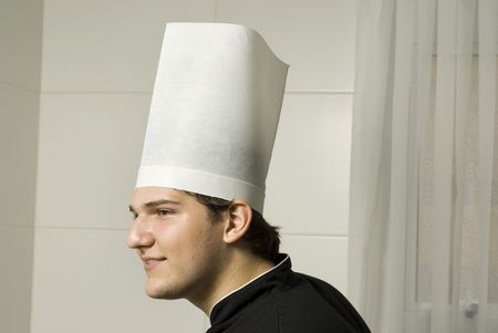 Smiling young chef in a chef's hat . Horizontally framed photo. Stock Photo - 3878242