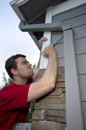 sufficient: Grimacing man fixing a house with a screwdriver. Vertically framed photo.