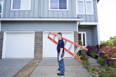 Smiling man standing in front of house holding ladder and hammer. Horizontally framed photo. photo