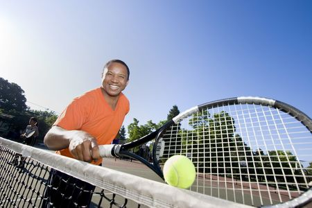 Man holding his racket and laughing. Horizontally framed shot. photo