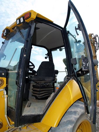 A Caterpillar Backhoe is parked at an excavation site with the door open.  Vertically framed shot. Stock Photo - 3881917