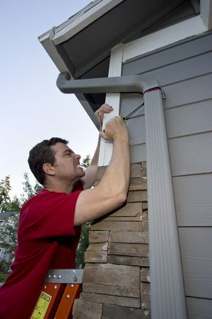 Grimacing man standing on a ladder fixing a house with a screwdriver. Vertically framed photo. photo