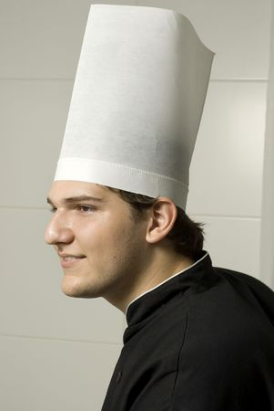 Smiling young chef in a chef's hat . Vertically framed photo. photo