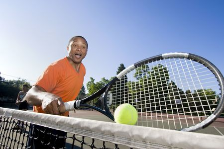 Man holding his racket making a silly face, his partner is in the background in a ready stance. Horizontally framed photo. Stock Photo - 3883255
