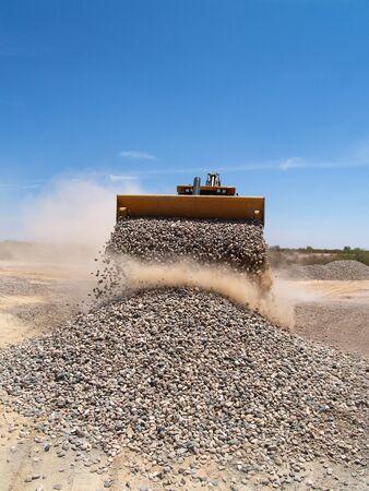 A giant backhoe is shoveling and dumping gravel on a desert excavation site.  Vertically framed shot.