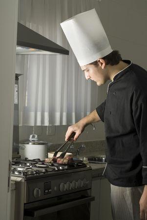 bakplaat: Jonge chef grillen steaks op een grillplaat op een kachel in een keuken. Verticaal ingelijste foto. Stockfoto