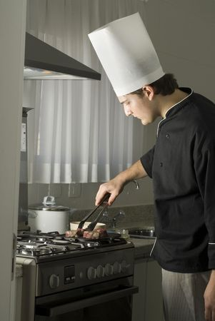 Young chef grilling steaks on a griddle on a stove in a kitchen. Vertically framed photo. photo