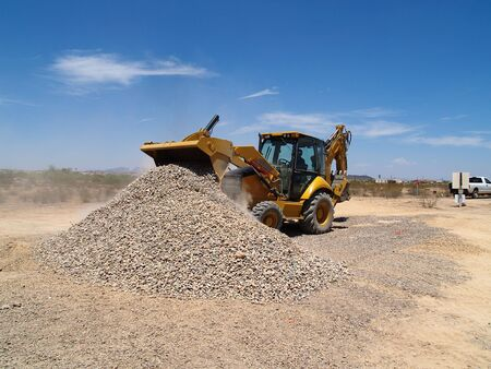 dumping: A giant backhoe is shoveling and dumping gravel on a desert excavation site.  Horizontally framed shot.