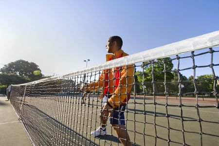 Man playing tennis. He holds his racket and stands near the net as he hits the tennis ball. Horizontally framed photo. photo