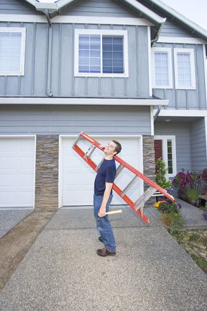 Laughing man standing in front of house holding ladder and hammer. Vertically framed photo. Stock Photo