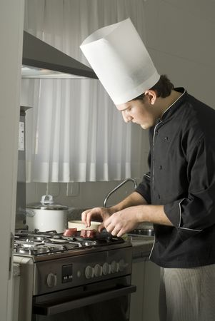 Chef standing over a stove grilling steaks. Vertically framed photo.