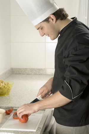Young, smiling chef in a kitchen slicing tomatoes in a bowl. Vertically framed photo. photo