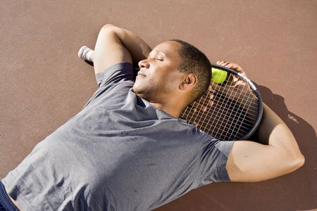 tired: Tennis player laying down sleeping on the court with his ball and racket. Horizontally framed photo. Stock Photo