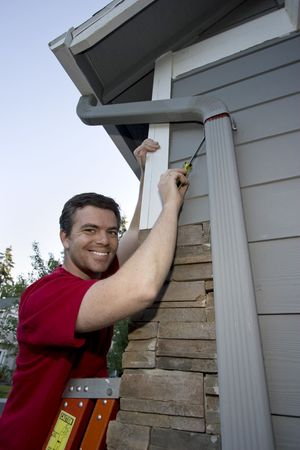 Smiling man standing on a ladder fixing a house with a screwdriver. Vertically framed photo. photo